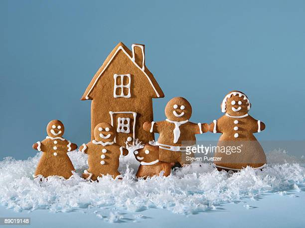 Gingerbread family in front of gingerbread house