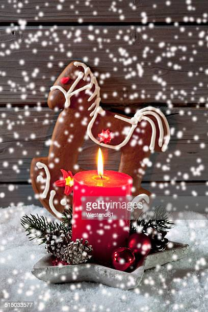 Gingerbread horse, lighted red candle and Christmas bubbles with rippling artificial snow in front
