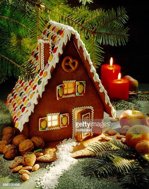 A gingerbread house surrounded by nuts and apples