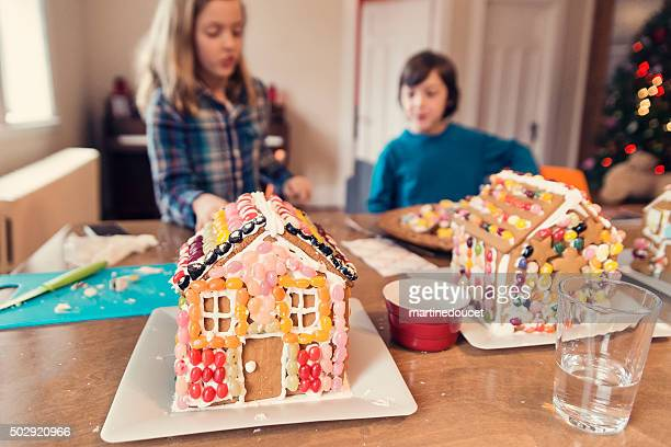 Gingerbread houses decorated with candy on messy table.