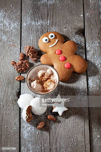 Gingerbread man, Christmas cookies and a mug of cocoa with cream on grey wood