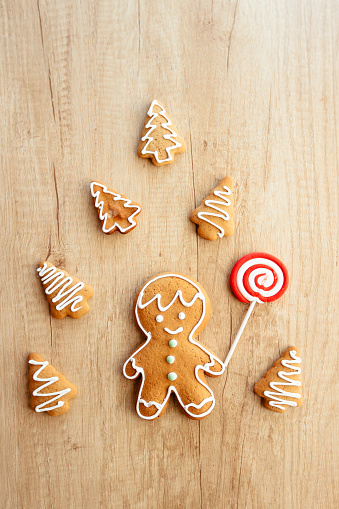 Gingerbread man cookie surrounded by Christmas tree cookies on the wooden table, high angle view - gettyimageskorea