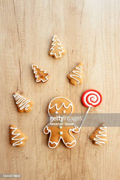 Gingerbread man cookie surrounded by Christmas tree cookies on the wooden table, high angle view