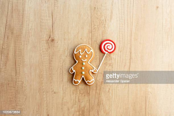 gingerbread man holding lollipop on a wooden background - gingerbread man stock photos and pictures
