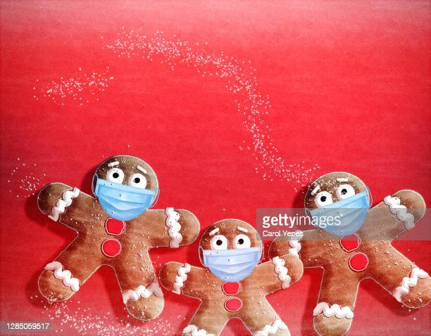 gingerbread man with surgical mask in red background - gingerbread men stock pictures, royalty-free photos & images