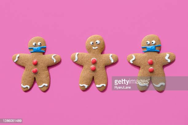 gingerbread men christmas cookies wearing protective face masks - gingerbread men stock pictures, royalty-free photos & images