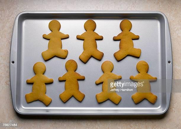 gingerbread men on baking sheet - baking sheet stock pictures, royalty-free photos & images