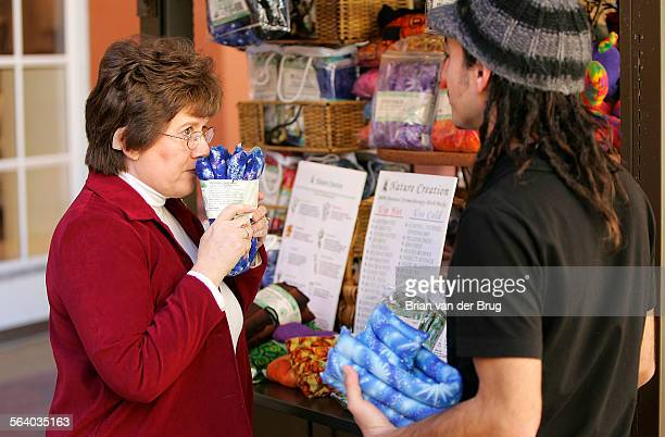 Ginny Baker left smells scented aromatherapy products as shopkeeper Lior Netzer right describes the items to her at the Simi Valley Town Center...