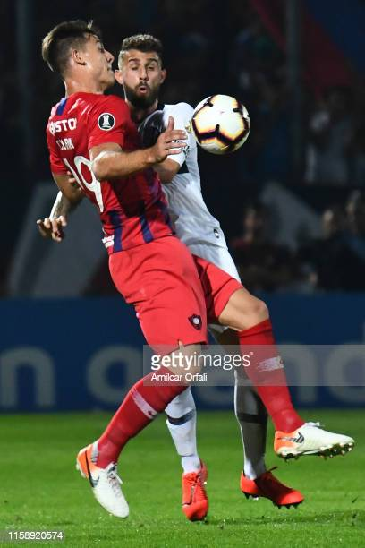 Gino Peruzzi of San Lorenzo fights for the ball with Diego Churin of Cerro during a round of sixteen second leg match between Cerro Porteño and San...