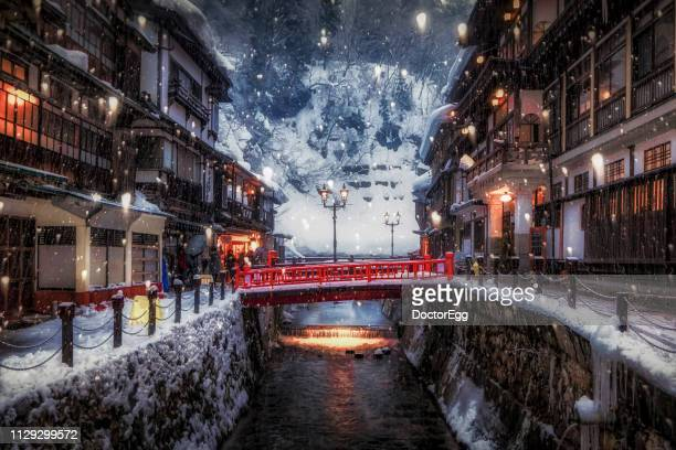 ginzan onsen with snow falling in winter, yamagata, japan - famous place ストックフォトと画像