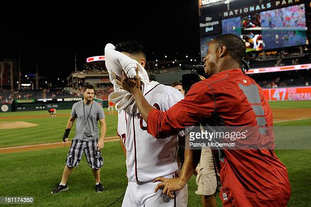 Gio Gonzalez is smeared with a shaving cream pie by Edwin Jackson of the Washington Nationals after a game against the St Louis Cardinals at...