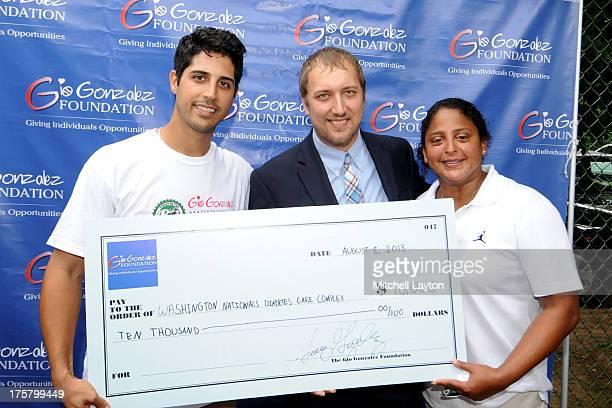 Gio Gonzalez Maxwell Houston of Children's Hospital and Romy Jimenez of the Gio Gonzalez Foundation present a check to the Washington Nationals...