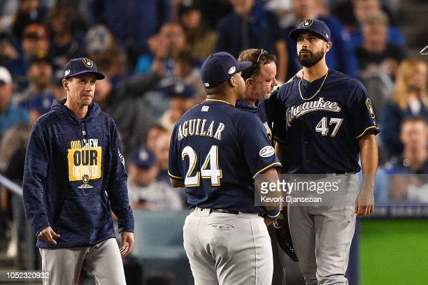 Gio Gonzalez of the Milwaukee Brewers is looked at by the trainer and manager Craig Counsell after being injuried during the second inning against...