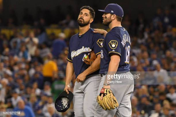 Gio Gonzalez of the Milwaukee Brewers reacts with Mike Moustakas after he was injured during the second inning against the Los Angeles Dodgers in...