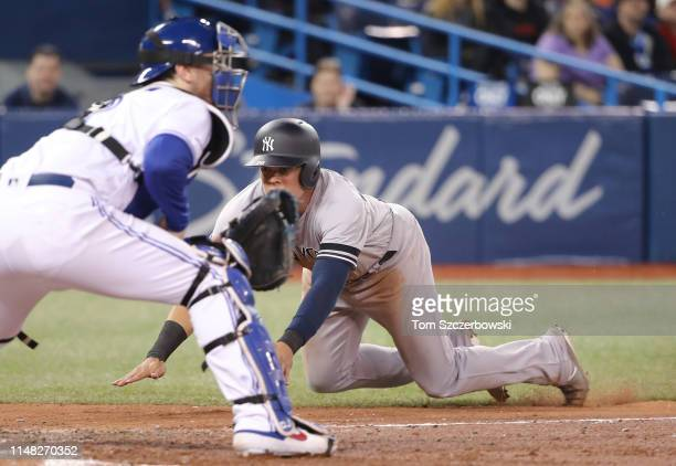 Gio Urshela of the New York Yankees slides across home plate to score a run in the fifth inning during MLB game action as Danny Jansen of the Toronto...