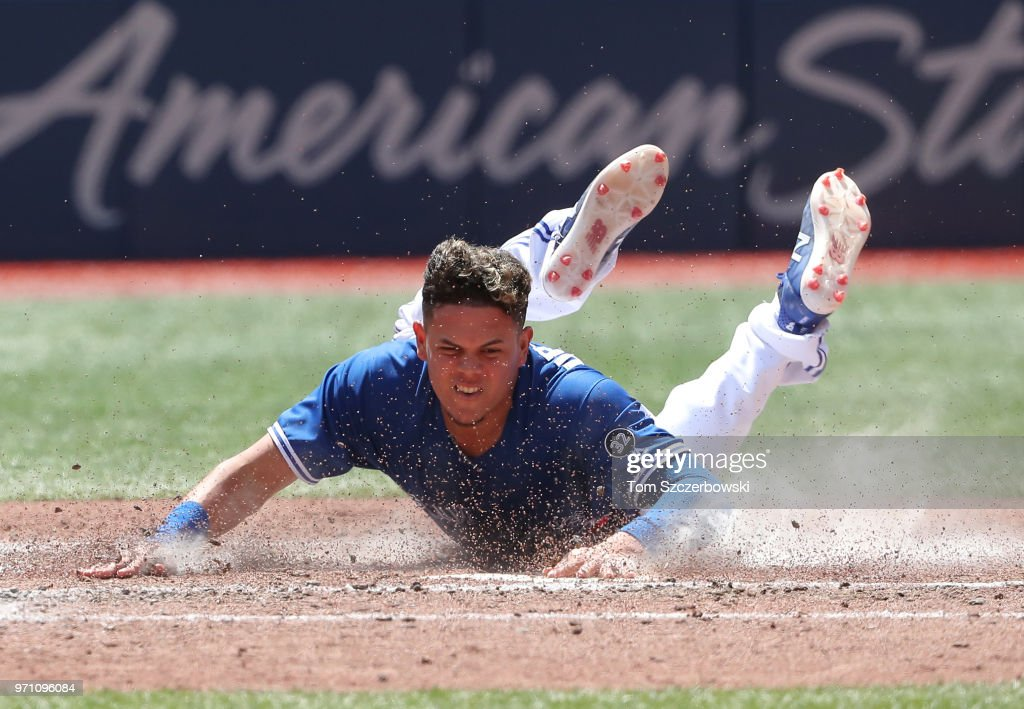 Gio Urshela #3 of the Toronto Blue Jays slides safely across home plate to score a run in the fifth inning during MLB game action against the Baltimore Orioles at Rogers Centre on June 10, 2018 in Toronto, Canada.