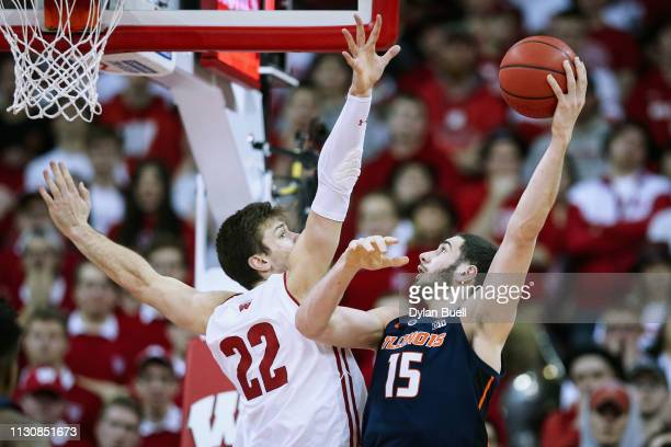 Giorgi Bezhanishvili of the Illinois Fighting Illini attempts a shot while being guarded by Ethan Happ of the Wisconsin Badgers in the second half at...