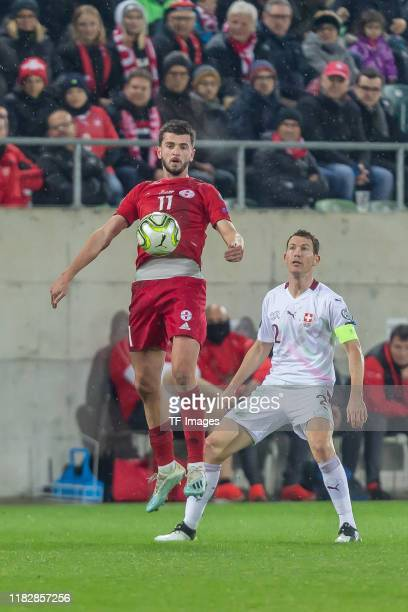Giorgi Kvilitaia of Georgia and Stephan Lichtsteiner of Switzerland battle for the ball during the UEFA Euro 2020 Qualifier between Switzerland and...