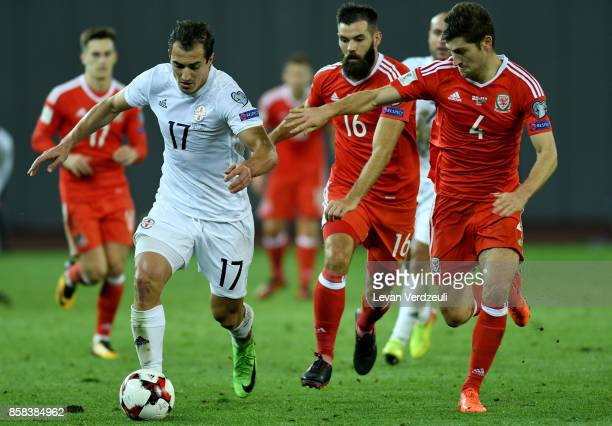 Giorgi Merebashvili of Georgia in action with Joe Ledley and Ben Davies of Wales in action during the FIFA 2018 World Cup Qualifier between Georgia...