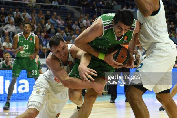 Giorgi Shermadini #17 of Unicaja and Jonas Maciulis of Real Madrid in action during the Euroleague basketball match between Real Madrid and Unicaja...