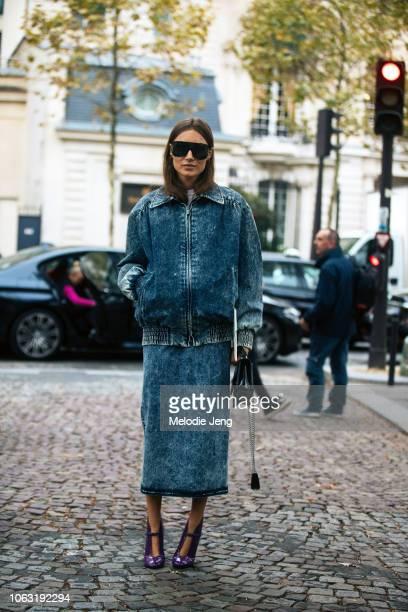 Giorgia Tordini wears black sunglasses acidwash jacket and skirt Miu Miu purse and purple heels before the Miu Miu show during Paris Fashion Week...