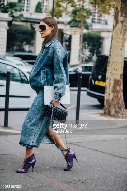 Giorgia Tordini wears black sunglasses, acid-wash jacket and skirt, Miu Miu purse, and purple heels before the Miu Miu show during Paris Fashion Week...