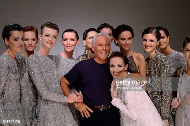 Giorgio Armani pases for photographs with a group of models in Milan Italy