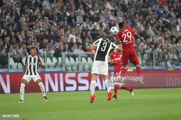 Giorgio Chiellini and Emmanuel Emenike compete for the ball during the UEFA Champions League football match between Juventus FC and Olympiakos FC at...