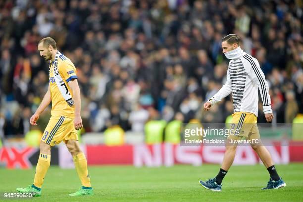 Giorgio Chiellini and Mattia De Sciglio walk off the pitch dejected during the UEFA Champions League Quarter Final Second Leg match between Real...