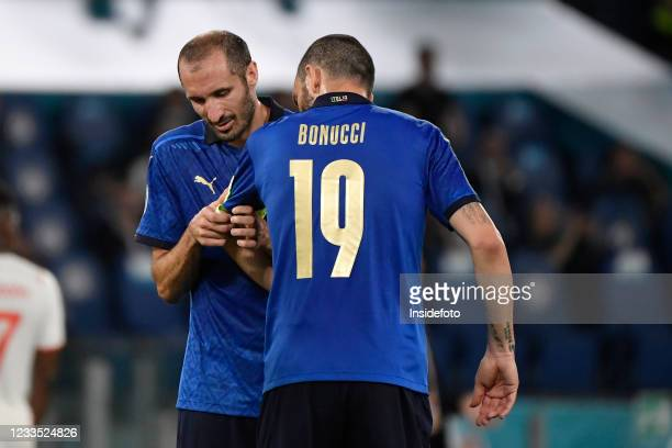 Giorgio Chiellini of Italy, injured, gives the captain arm band to Leonardo Bonucci during the Uefa Euro 2020 Group A football match between Italy...
