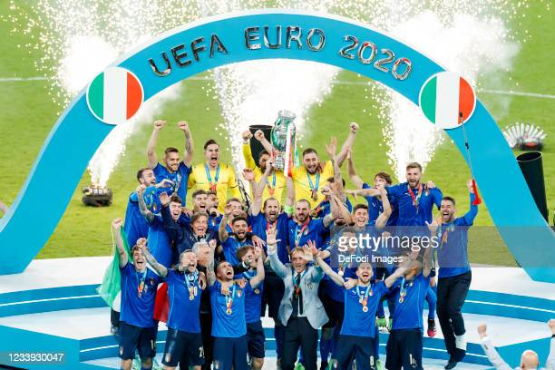 Giorgio Chiellini of Italy lifts the trophy while his team-mates celebrate after winning the UEFA Euro 2020 Championship Final between Italy and...
