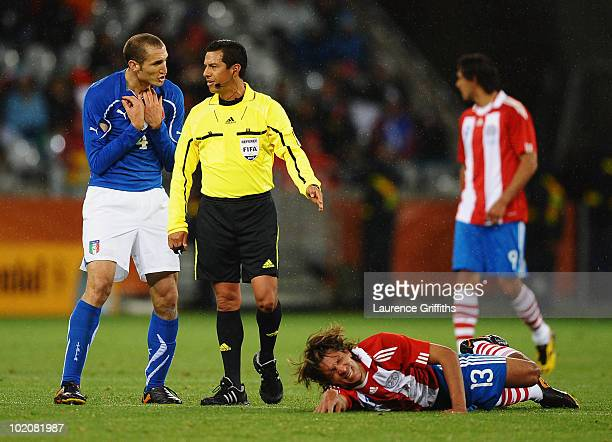 Giorgio Chiellini of Italy pleads his innocence to referee Benito Archundia as Enrique Vera of Paraguay lies on the ground injured during the 2010...