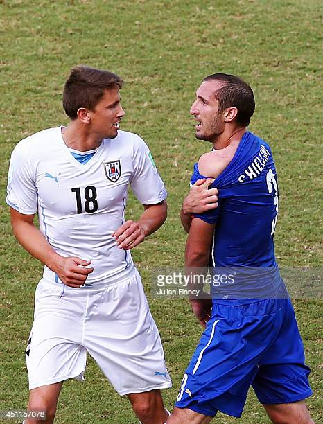 Giorgio Chiellini of Italy pulls down his shirt after a clash with Luis Suarez of Uruguay as Gaston Ramirez of Uruguay looks on during the 2014 FIFA...