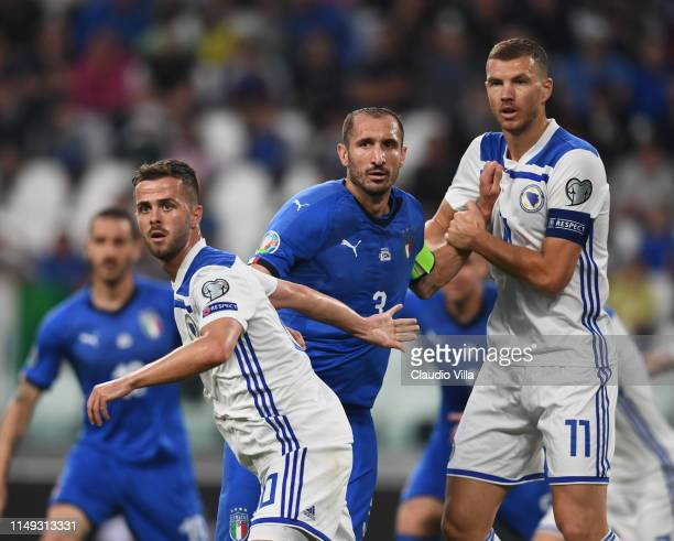 Giorgio Chiellini of Italy struggles with Edin Dzeko and Miralem Pjanic of Bosnia during the UEFA Euro 2020 Qualifier between Italy and Bosnia and...