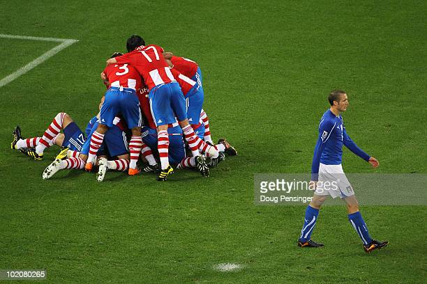 Giorgio Chiellini of Italy walks away dejected as the Paraguay players celebrate after Antolin Alcaraz of Paraguay scores the opening goal during the...