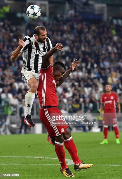 Giorgio Chiellini of Juventus and Emmanuel Emenike of Olympiacos competes for the ball during the UEFA Champions League group D match between...