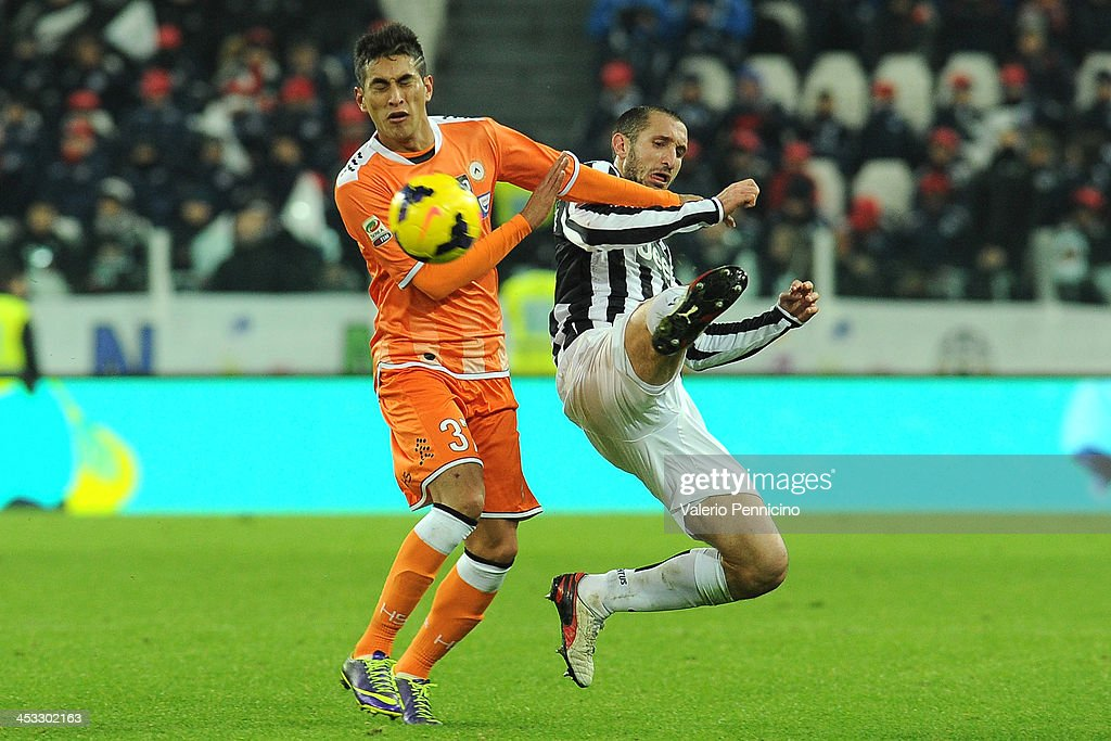 Giorgio Chiellini (R) of Juventus is tackled by Bruno Fernandes of Udinese Calcio during the Serie A match between Juventus and Udinese Calcio at Juventus Arena on December 1, 2013 in Turin, Italy.