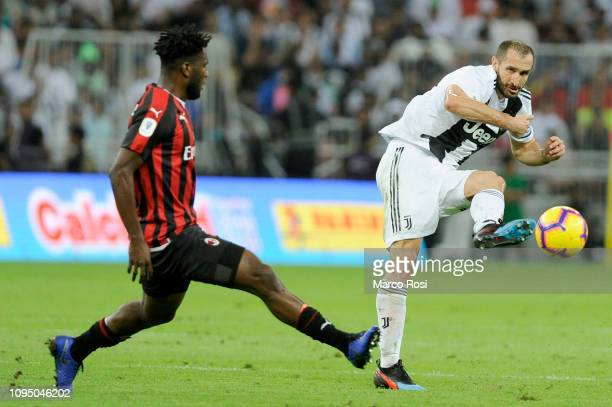 Giorgio Chiellini of Juventus passes the ball under pressure from Franck Kessie of AC Milan during the Italian Supercup match between Juventus and AC...