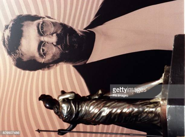 Giorgio de Chirico's 'Ettore E Andromaca' stands in front of a poster of rock legend Eric Clapton at Christies in London today before the...