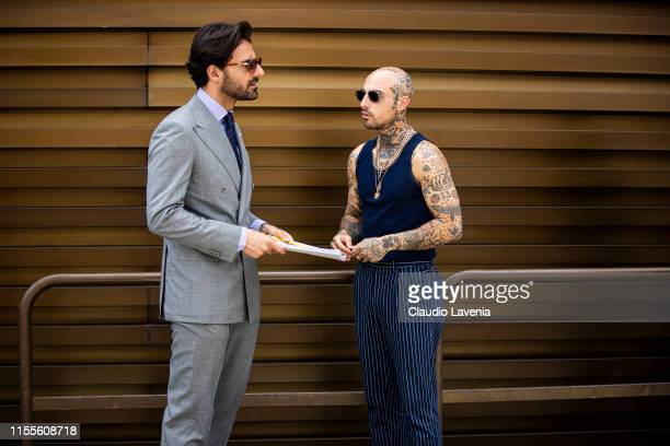 Giorgio Giangiulio wearing a grey suit light purple shirt and blue necktie and Roberto Malizia wearing a blue sleveless top and blue striped pants...