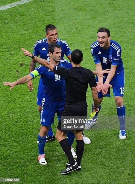 Giorgos Karagounis and Vasilis Torosidis of Greece appeal to Referee Carlos Velasco Carballo for handball during the UEFA EURO 2012 group A match...
