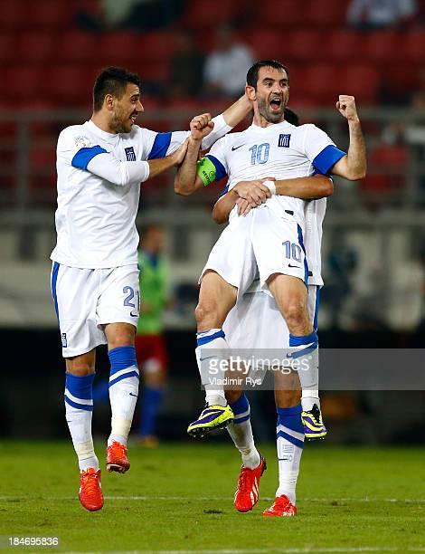 Giorgos Karagounis of Greece celebrates scoring with team mates Kostas Katsouranis and Dimitris Siovas after scoring his team's second goal during...
