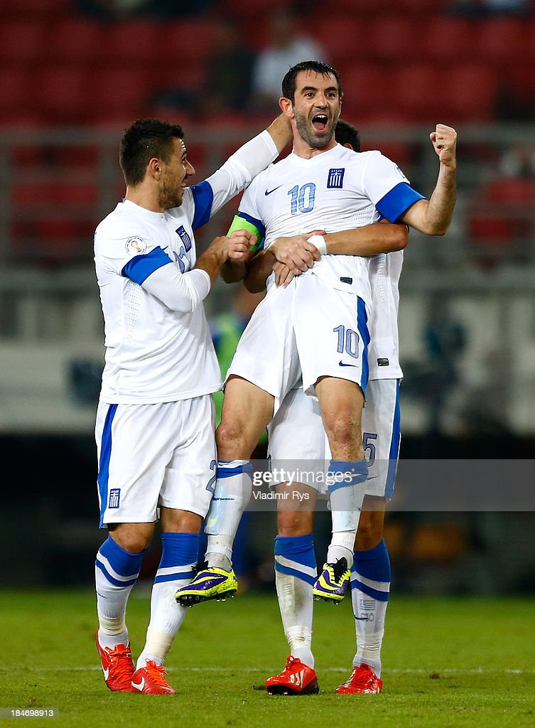 Giorgos Karagounis of Greece is celebrated by his team mates Kostas Katsouranis (L) and Dimitris Siovas after scoring his team's second goal during the group G FIFA 2014 World Cup Qualifier match between Greece and Liechtenstein at Karaiskakis Stadium on October 15, 2013 in Athens, Greece.
