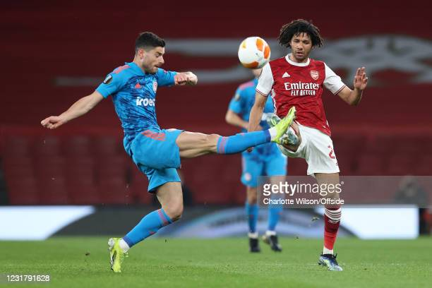 Giorgos Masouras of Olympiacos battles with Mohamed Elneny of Arsenal during the UEFA Europa League Round of 16 Second Leg match between Arsenal and...