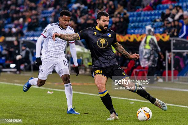 Giorgos Merkis of Apoel defends the ball from Eric Ramires of Basel during the UEFA Europa League round of 32 second leg match between FC Basel and...