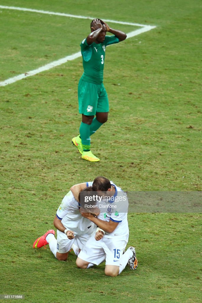 Giorgos Samaras (L) and Vasilis Torosidis of Greece celebrate after being awarded a penalty kick late in the match as a dejected Arthur Boka of the Ivory Coast looks on during the 2014 FIFA World Cup Brazil Group C match between Greece and the Ivory Coast at Castelao on June 24, 2014 in Fortaleza, Brazil.