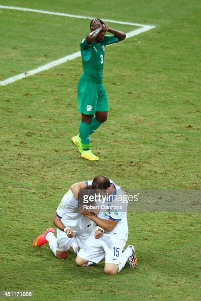 Giorgos Samaras and Vasilis Torosidis of Greece celebrate after being awarded a penalty kick late in the match as a dejected Arthur Boka of the Ivory...