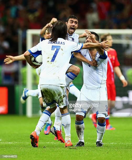 Giorgos Samaras, Giannis Maniatis and Giorgos Tzavelas of Greece celebrate victory and progress to the quarter finals during the UEFA EURO 2012 group...