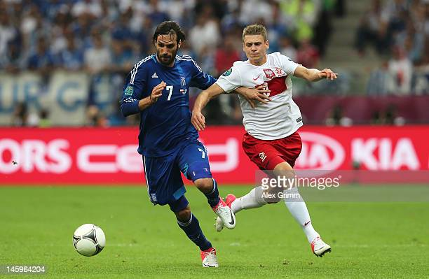 Giorgos Samaras of Greece and Lukasz Piszczek of Poland battle for the ball during the UEFA EURO 2012 group A match between Poland and Greece at...
