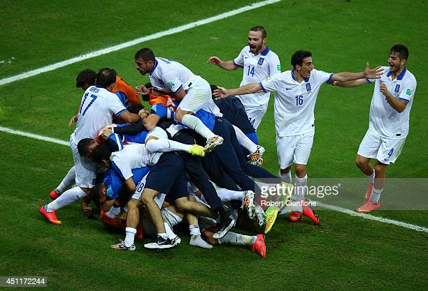 Giorgos Samaras of Greece celebrates with teammates after scoring his team's second goal on a penalty kick during the 2014 FIFA World Cup Brazil...